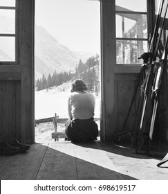 Woman sitting at doorstep of mountain hut