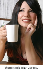 Woman sitting down with a cup of hot coffee
