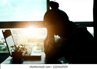 woman sitting down, his face unsettled. At the computer desk she has headaches and stress. Cause of hard work and insufficient rest.