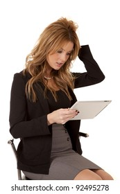 A woman sitting down and looking at her tablet with a frustrated expression on her face.