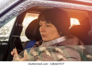 A woman sitting in the driver's seat and looking at the phone, close-up