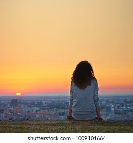 A woman is sitting at ease by the city during sunset moment.