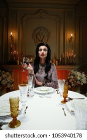 Woman sitting at end of the set dinner table holding glass in room lit with candles
