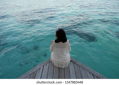 A woman is sitting enjoying the scenery at the pulo cinta Gorontalo resort in Indonesia