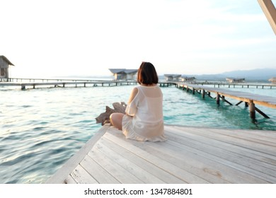 A woman is sitting enjoying the scenery at the pulo cinta resort Gorontalo Indonesia