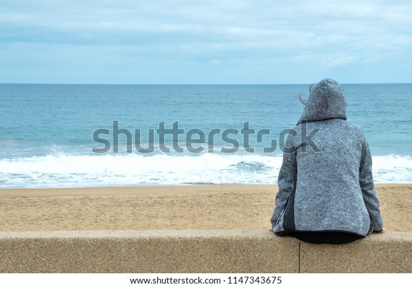 Woman sitting in front of the beach and the blue sea