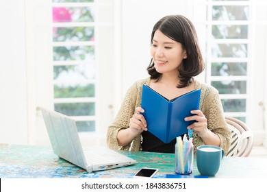本を持ってコンピューターの前に座る女性