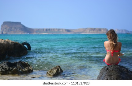 The woman sitting in front of the islands and the Aegean Sea