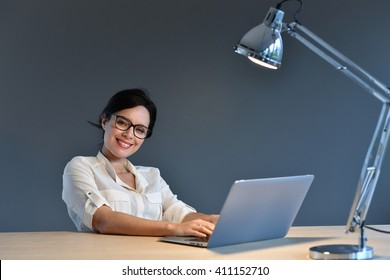 Woman sitting in front of laptop, isolated