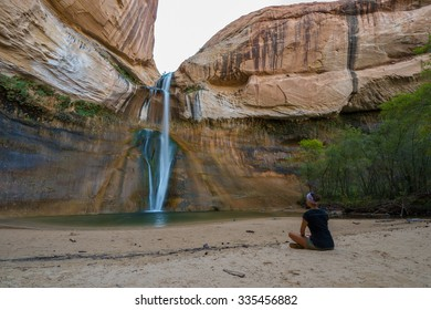 Woman Sitting in front of the Lower Calf Creek Falls, Calf Creek, Grand Staircase-Escalante National Monument, south Utah, USA