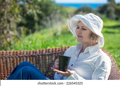 Woman sitting  in the garden  and holding a  cup of coffee