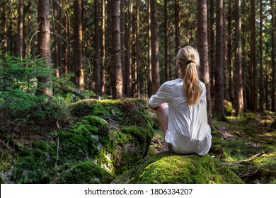 Woman sitting in green forest enjoys the silence and beauty of nature. - Shutterstock ID 1806334207