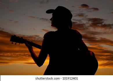 A woman is sitting with a guitar in the sunset.