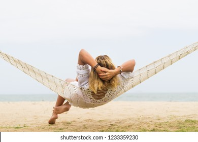 Woman sitting in hammock on the beach. Travel and vacation concept.