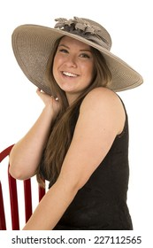 A woman sitting in her chair with a big smile on her face wearing her hat.