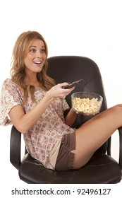 A woman sitting in her chair with a tv remote and a bowl of popcorn.
