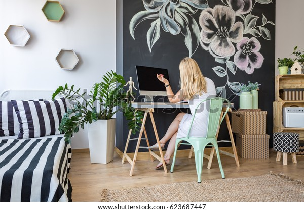 Woman is sitting at her desk in bright cozy atelier