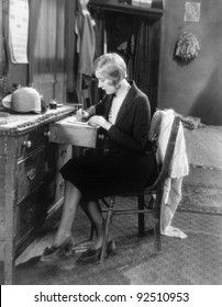 Woman sitting at her desk writing a letter