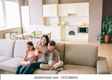Woman is sitting with her kids and looking straight. Girl eats popcorn. Boy is using remote control from TV. Woman holds it as well.