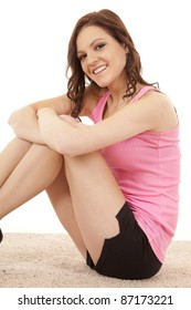 A woman is sitting in her workout clothes ready to exercise.
