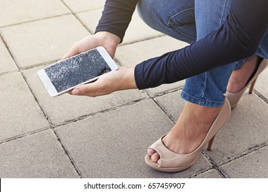 Woman is sitting and holding a broken smart phone with a cracked screen