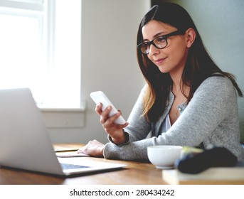 Woman sitting in home office at desk smirking and checking mobile phone.
