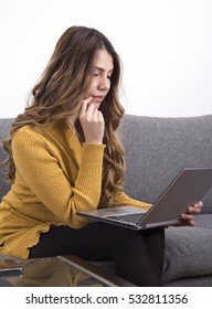 Woman sitting in home working with her laptop