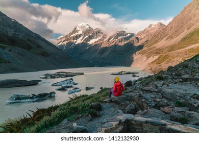 Woman sitting at ice Glacier lake at the top of Mount Cook from the Hooker trail tramping trek. Dramatic. Snow capped Mountain background. Grey red moody. Shot in Pukaki South Island, New Zealand.
