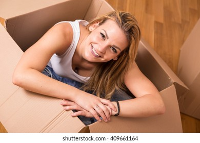 Woman sitting inside a cardboard box while packing