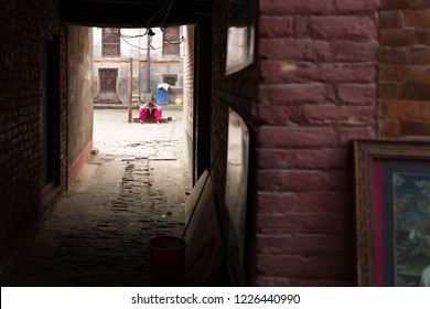 A woman sitting inside a courtyard at the end of an alley in Nepal