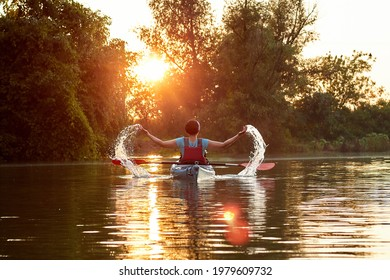 A woman sitting in a kayak waving her arms like a butterfly. Splashing water and hands like butterfly wings