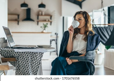 Woman sitting at kitchen table with laptop drinking from a mug