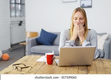 woman sitting at laptop at home holding her hands on her mouth afraid of a computer virus or a mistake