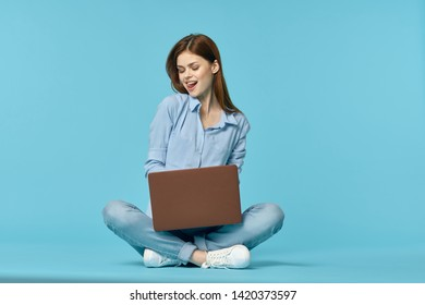 woman sitting with a laptop on the floor