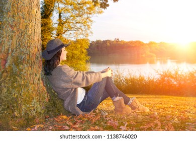 Woman sitting leaning on tree in the park