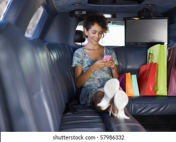 woman sitting in limousine with shopping bags and typing on mobile phone. Horizontal shape, full length, copy space