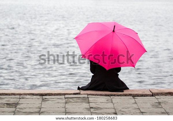 Woman sitting lonely with pink umbrella. Concept of taking a break, solitude and thinking with good copyspace on water.