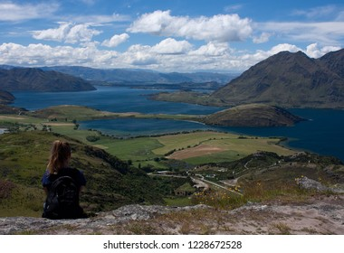 A woman sitting and looking at the Lake Wanaka near the town Wanaka in New Zealand