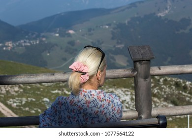 Woman is sitting and looks at mountains