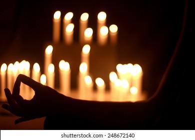 Woman sitting in lotus pose beside white candles
