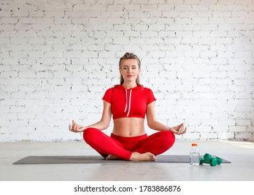 The woman is sitting in the lotus position with closed eyes. Lotus position, meditation and calmness.