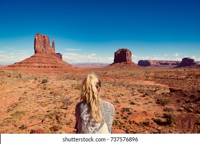 woman sitting in Monument Valley with red rocks overview. Arizona