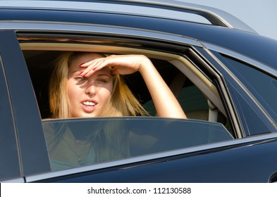 Woman sitting in a motor car peering into the sun through the half open window with her hand shielding her eyes