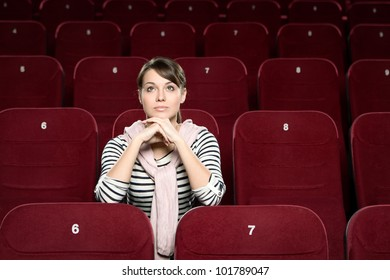 A woman sitting in the movie theatre