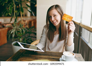 Woman sitting near big window in coffee shop at table with credit card, cup of coffee, cake, relaxing in restaurant during free time. Female working on tablet computer rest cafe. Lifestyle concept