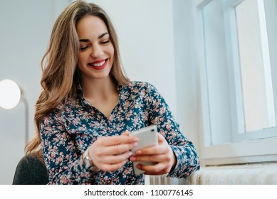 Woman sitting near window and checking message on phone.