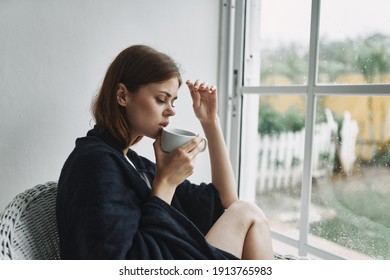 woman sitting near the window with a cup of coffee interior comfort