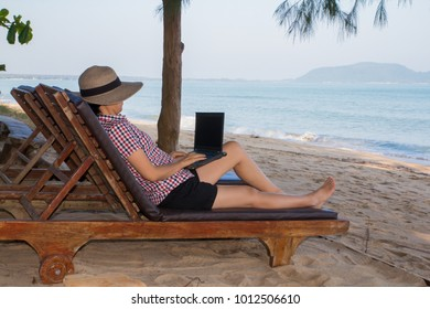 woman is sitting with a notebook on beach and blue sea view.