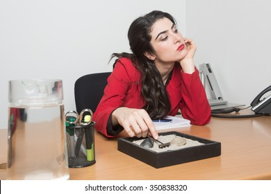 Woman sitting in the office bored playing with a zen garden