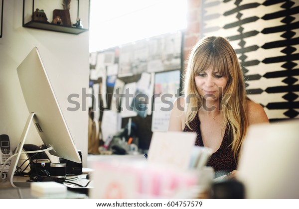 Woman sitting in an office at a desk with a computer, working